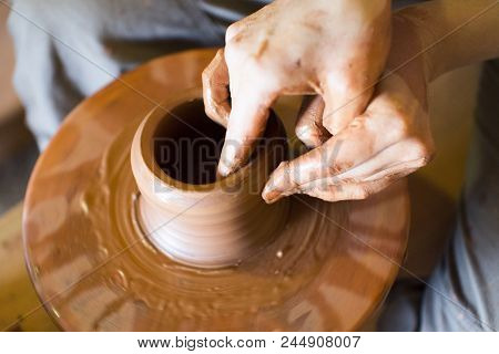 Rotating Potter's Wheel And Clay Ware On It Vase : Taken From Above. Hands In Clay. Pottery: Male Ce