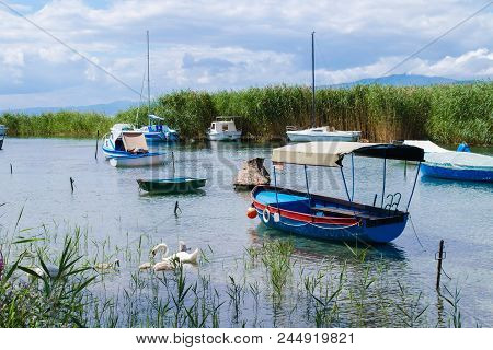 Small boats sit by the reeds at the mouth of the Black Drin River on Lake Ohrid poster