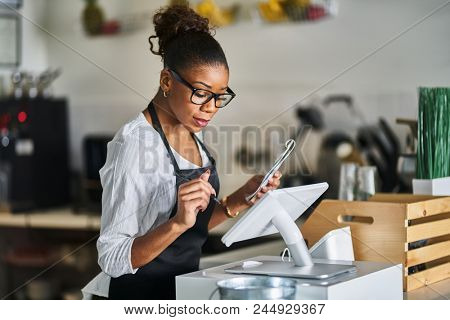 shop assistant placing order from notepad into pos point of sale terminal at register in restaurant