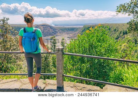 Hawaii hiking travel tourist hiker girl looking at view of Kilauea Iki crater lava field lake in Big Island, Hawaii. United states of America summer vacation popular attraction.