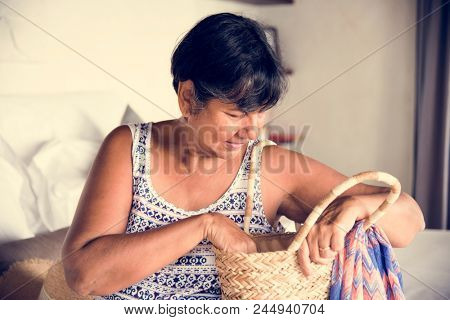 Mature woman unpacking her clothes