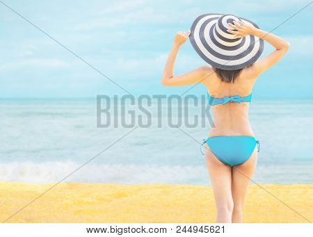 Young Beautiful Sexy Woman Wearing Bikini And Relaxing On The White Sandy Beach Near The Waves Of Bl