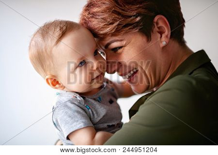 Tenderness between mom and male baby in her hands