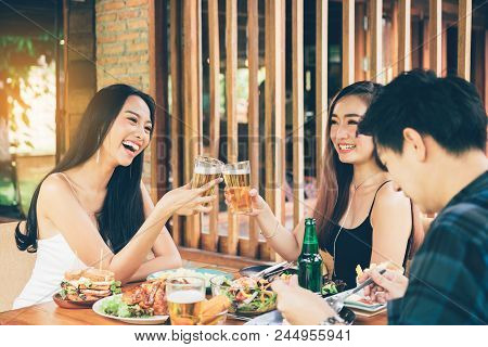 Teeneger Asian Friends Clinking Glasses While Enjoying An Evening Meal In A Restaurant.