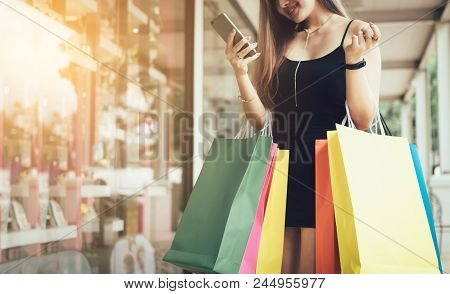 Asian Woman Using Smartphone And Message To Friendship After Shopping.