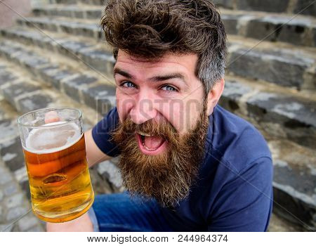 Guy having rest with draught beer. Hipster on cheerful smiling face drinks beer outdoor. Man with beard and mustache holds glass with beer while sits on stone stairs, defocused. Celebration concept. poster