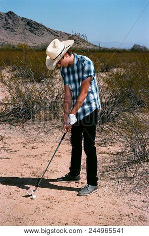 Young Boy In Natural Terrain Desert Golfing
