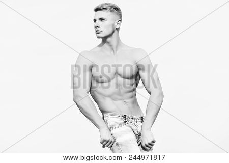 Man Posing On Sky Background With Serious Face. Young Handsome Man With Sexy Muscular Athletic Stron