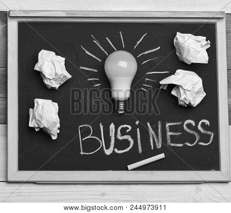 Idea Concept. Grey Board With Idea Lamp, Paper And Chalk. Crumpled Paper And White Lamp As Symbol Of