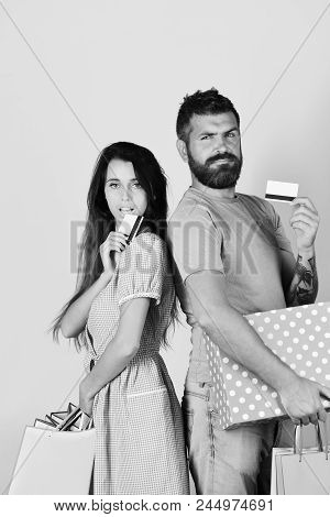 Guy With Beard And Girl With Serious Faces Do Shopping. Shopping And Spending Concept. Couple In Lov