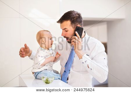 A Baby Boy Making His Fathers Tie Dirty When Eating. A Young Man With Smartphone, Feeding His Son An
