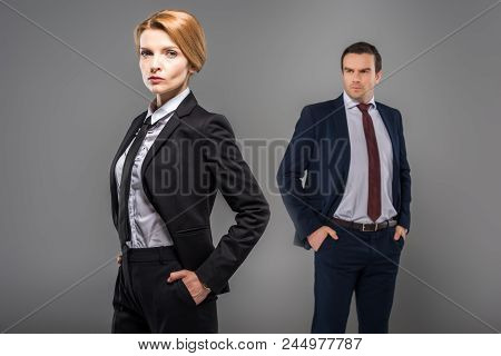 Confident Businesswoman With Hands In Pockets And Businessman Standing Behind, Isolated On Grey, Fem