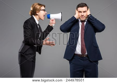Angry Businesswoman With Bullhorn Screaming At Businessman, Isolated On Grey, Feminism Concept