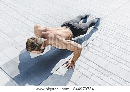 Fit Fitness Man Doing Fitness Exercises Outdoor At City Background. He Doing Hamstring Leg Exercise