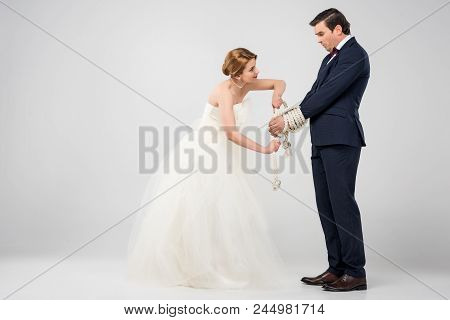 Bride In Wedding Dress Bounding Groom With Rope, Isolated On Grey, Feminism Concept