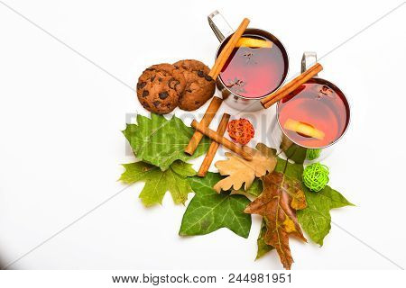 Mugs With Mulled Wine Or Hot Drink Near Autumn Leaves And Cookies On White Background, Close Up. Hot