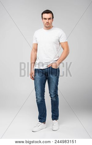 Handsome Man With Hand In Pocket Looking At Camera, Isolated On Grey