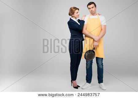 Businesswoman And Male Upset Householder With Frying Pan Hugging Together, Feminism Concept, Isolate