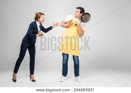 Businesswoman Yelling At Scared Husband With Frying Pan, Feminism Concept, Isolated On Grey