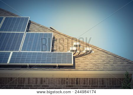 Close-up solar panel system on asphalt shingles rooftop surround green tree. End run, junction box, enclosure bracket installation at Grapevine, Texas, USA. Rail-less racking module, renewable energy poster