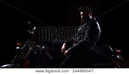 Man With Beard, Biker In Leather Jacket Sitting On Motor Bike In Darkness, Black Background. Macho,