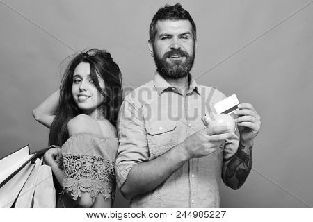 Couple In Love Holds Shopping Bags On Green Background. Shopping And Spending Concept. Guy With Bear
