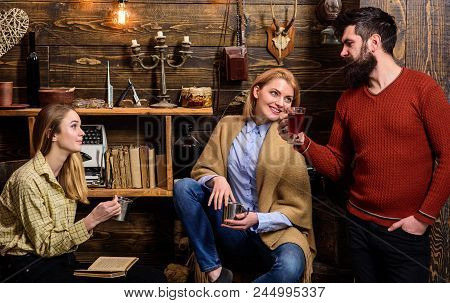 Friends, family spend pleasant evening, interior background. Girls and man on happy faces hold metallic mugs, enjoy coziness with drinks. Coziness concept. Friends drinking tea and chatting. poster