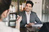 Business, career and placement concept - smiling caucasian man 30s negotiating with committee of businesslike people during job interview in office poster