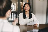 Business, career and placement concept - joyful asian woman smiling and holding resume while sitting in front of directors during corporate meeting or job interview poster