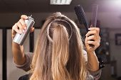 hairdresser making a coiffure to a young model in a beauty salon. woman is holding a hair spray and combs. concept of professional stylist studying poster