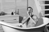 man in the bathroom. Sexuality and relaxation concept. Guy in bathroom with toiletries and stairs on background. Man with beard and scared face with hands on face. Macho sitting naked in bathtub covered with foam. poster