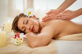 Beautiful woman enjoying during a back massage with warm stones at a spa. poster