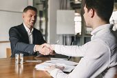 Business, career and placement concept - successful young man smiling and handshaking with european businessman after successful negotiations or interview in office poster