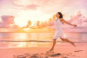 Freedom wellness well-being happiness concept. Happy carefree Asian woman feeling blissful jumping of joy on peaceful beach at sunset. Serenity, relaxation, mindfulness, stress free concepts. poster