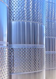 Stainless Steel Wine Fermentation Vats In A Winery Outdoors Reflecting Sky And Ground