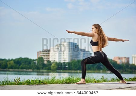 Yoga Female With Long Hair Standing In A Warrior Pose, Virabhadrasana Near A River In The Background
