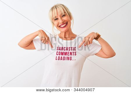 Middle age woman wearing fanny t-shirt with irony comments over isolated white background very happy pointing with hand and finger