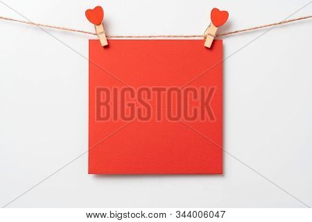 Red Note Paper Sticker Concept. Valentines Day Background. Symbol Of Love, Copy Space. Clothes Pegs