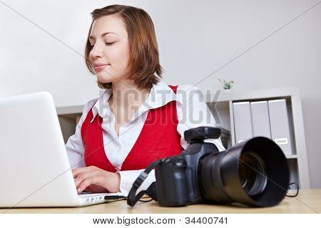 Professional photographer copying images from DSLR camera to laptop computer
