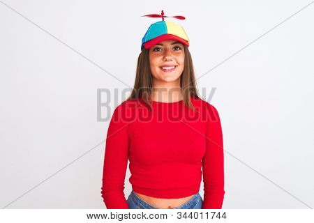 Young beautiful girl wearing fanny cap with propeller standing over isolated white background with a happy and cool smile on face. Lucky person.