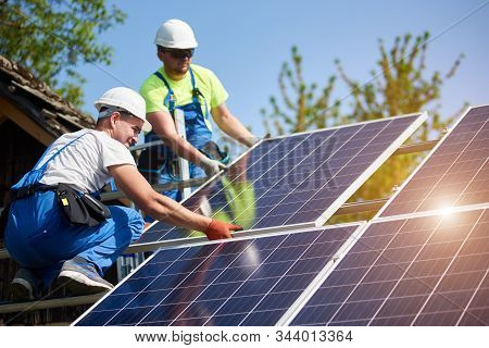 Two Professional Technicians Installing Heavy Solar Photo Voltaic Panels To High Steel Platform. Ext
