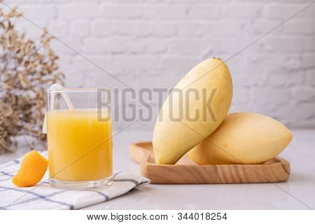 Glass Of Mangoes Juice And Mangoes  On Table.