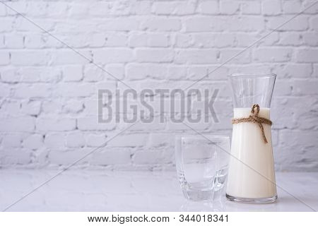 Kitchen Table With Bottle Of Milk On Brick Wall.