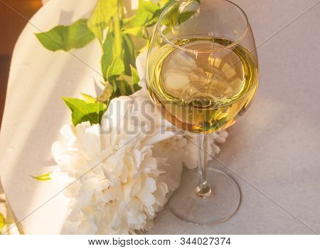 One Glass Of White Wine And A White Peony Flower On A White Table, Top View. Relax With A Glass Of W