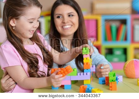 Cute Little Girl And Her Mother Playing