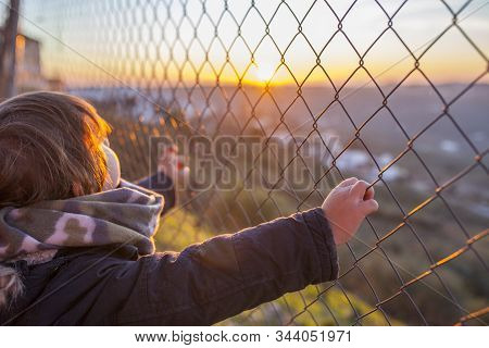 Kid Boy Holding Hands On Wire Fence At Sunset. Concept For Child Fredom, Abuse, Human Trafficking,