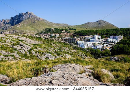 Cala Sant Vicent, Mallorca, Spain, 09-20-2018: View Of The City Of Cala Sant Vicent Surrounded By Mo