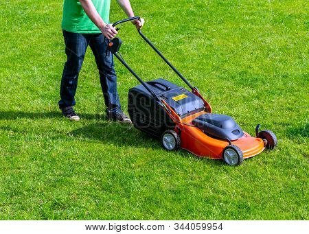 Man In Motion With Lawnmower And Mows Green Grass