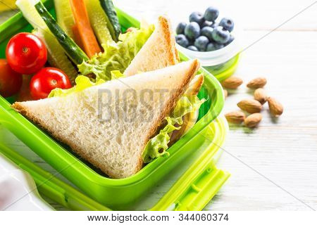School Lunch Box With Sandwich, Vegetables, Banana, Yogurt, Nuts And Berries On White Wooden Table.