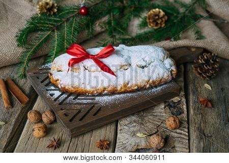 Stollen With Powdered Sugar And Red Ribbon Bow On Top Stands On Rustic Wooden Table.